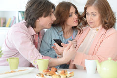 Happy family using mobile phone together Royalty Free Stock Photo
