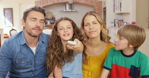 Happy family using remote on the sofa stock footage