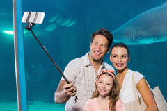 Happy family using selfie stick Stock Photos