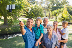Happy family using a selfie stick in the park Stock Photos