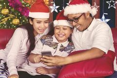 Happy family using a smartphone at Christmas time Royalty Free Stock Images