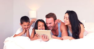 Happy family using tablet. In bed stock video