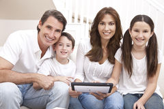 Happy Family Using Tablet Computer At Home. An attractive happy, family of mother, father, son and daughter sitting on a sofa at home having fun using a tablet Royalty Free Stock Image