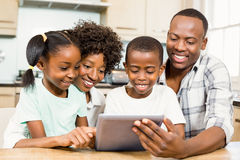 Happy family using tablet in kitchen Stock Photos