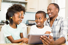 Happy family using tablet in kitchen. At home royalty free stock image