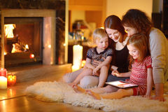 Happy family using a tablet pc by a fireplace. Happy young family using a tablet pc at home by a fireplace in warm and cozy living room on winter day Royalty Free Stock Photos