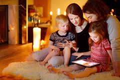 Happy family using a tablet pc by a fireplace Stock Image