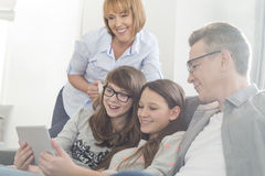Happy family using tablet PC on sofa at home Stock Photos