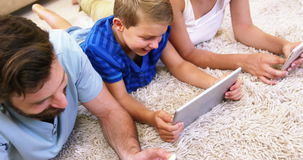 Happy family using tablet and smartphone lying on a carpet stock footage