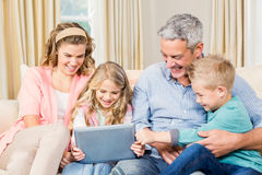 Happy family using tablet on the sofa Royalty Free Stock Photography