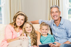 Happy family using tablet on the sofa Royalty Free Stock Photo