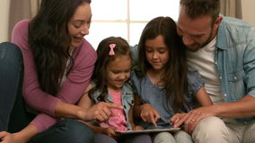 Happy family using tablet on the sofa stock footage