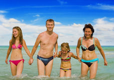 Happy family on vacation. Happy family walking in the sea holding each others hands Stock Photos