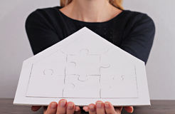 Happy family values, home insurance,real estate investment  concept. Woman holding house shape blank puzzle. Copy space image Stock Photo