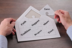 Happy family values : Love, Faith, Support, Share, Traditions, Respect, Trust. Man building house shape  puzzle close up Royalty Free Stock Image