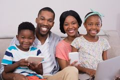 Happy family with various technologies sitting on sofa at home. Portrait of happy family with various technologies sitting on sofa at home Stock Photo