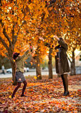 Happy family. Vertical photo,  happy beautiful little girl with mather throw up  autumnal leafage, in park Stock Photography