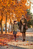 Happy family. Vertical photo,  happy beautiful little girl with mather  walking in park Royalty Free Stock Photo