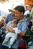 Happy family. Happy Vietnamese family in Mekong with smiling wife and laughing father holding baby, colorful background of bikes and motorbikes Royalty Free Stock Photography