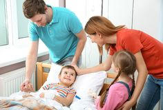Happy family visiting child in hospital. Happy family visiting little child in hospital stock photo
