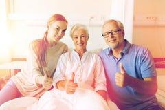 Happy family visiting senior woman at hospital Stock Photos