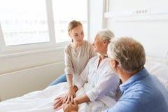 Happy family visiting senior woman at hospital Royalty Free Stock Photo