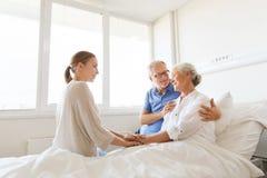 Happy family visiting senior woman at hospital Royalty Free Stock Images