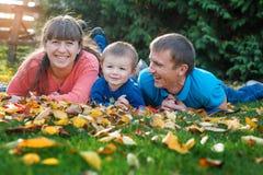 Happy family on walk in autumn park Stock Photos