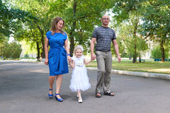 Happy family walk in city park, parents with child, summer season, green grass and trees Royalty Free Stock Image