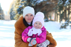 Happy family in walk: smilimg mother and little daughter in winter outdoors Stock Images