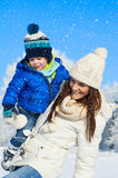 Happy family on the walk in sunny, winter day - snow falling Royalty Free Stock Photo