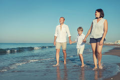 Happy family walk together on the sea surf line Royalty Free Stock Photography
