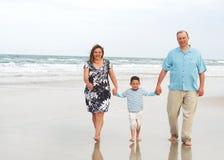 Family at the beach. Happy family walking along beach face forward royalty free stock photography