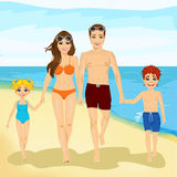 Happy family walking along a beach. Full length portrait of happy couple walking along a beach Royalty Free Stock Images
