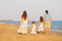 Happy family walking along the sea on the beach. At sunset. Parents and children are dressed in similar clothes Stock Images