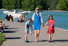 Happy family walking on Annecy lake embankment. Haute-Savoie, France stock photos