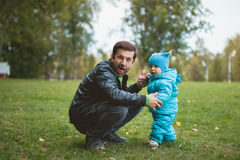 Happy family walking in autumn park: Adorable father and sun having fun together stock images
