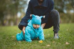 Happy family walking in autumn park: boy crawling on the grass with mother Stock Photo