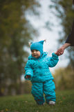 Happy family walking in autumn park: a boy runs on the field with the help of the mother Royalty Free Stock Image