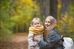 Happy family walking in autumn park - The mother and her daughter posing among the yellow leaves Royalty Free Stock Images