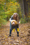 Happy family walking in autumn park - The mother playing with her daughter among the yellow leaves Royalty Free Stock Photography