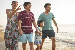 Happy family walking on the beach Stock Images