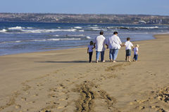 Happy family walking on the beach Royalty Free Stock Images