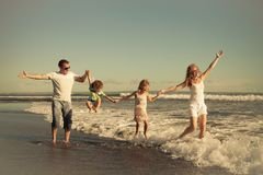 Happy family walking on the beach at the day time. Concept of friendly family stock images