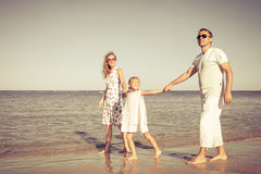 Happy family walking at the beach at the day time. Royalty Free Stock Photo