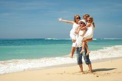 Happy  family  walking on the beach. Happy family walking at the beach at the day time. Concept of friendly family Royalty Free Stock Photos