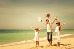 Happy  family  walking on the beach at the day time. Stock Photos