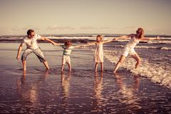 Happy family walking on the beach at the day time. Concept of friendly family on vacation Royalty Free Stock Images
