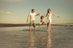 Happy family walking on the beach at the day time. Concept of friendly family on vacation Stock Images