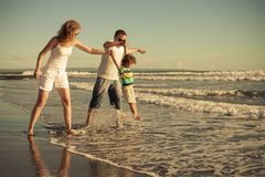 Happy family walking on the beach at the day time. Concept of friendly family on vacation Royalty Free Stock Photography